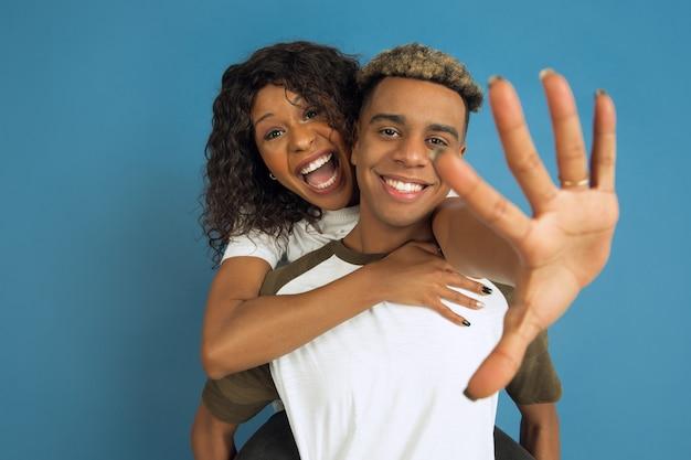 Jeune homme émotionnel et femme en vêtements décontractés blancs posant sur bleu.