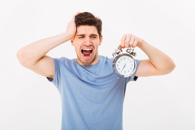 Jeune homme endormi 30s aux cheveux bruns tenant le réveil et le bâillement le matin, isolé sur mur blanc