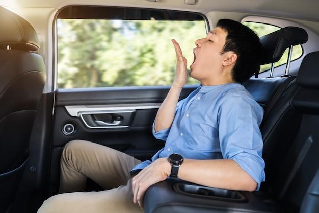Jeune homme endormi bâillant alors qu'il était assis sur le siège arrière de la voiture
