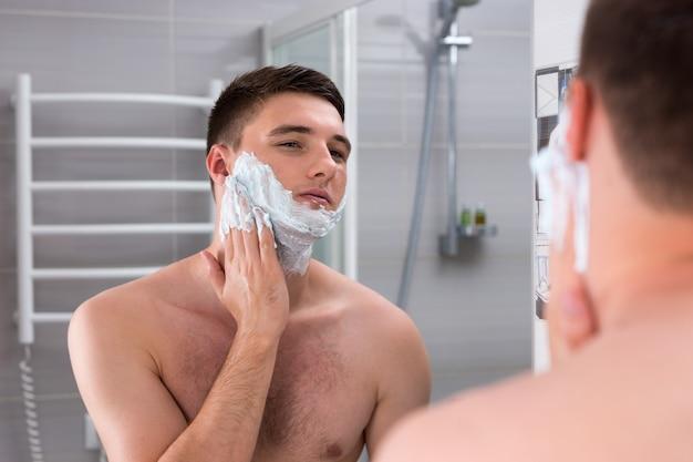 Jeune homme enduit de mousse pour se raser le visage debout devant un miroir dans la salle de bains carrelée moderne à la maison