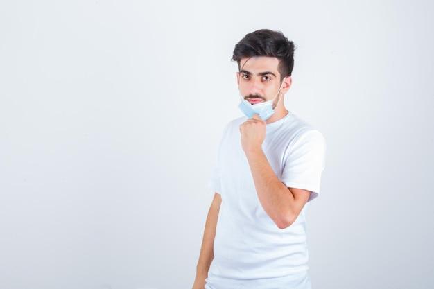 Jeune homme enlevant son masque en t-shirt blanc et ayant l'air confiant