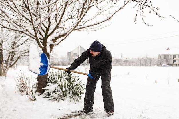 Le jeune homme enlève la neige près de la maison de banlieue