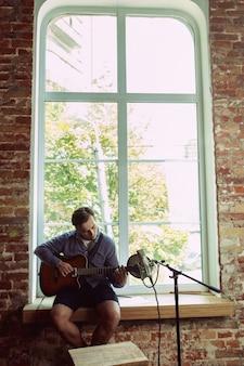 Jeune homme enregistrant un blog vidéo musical, une leçon à domicile ou une chanson, jouant de la guitare ou faisant un tutoriel sur internet tout en étant assis dans un loft ou à la maison concept de passe-temps, musique, art et création.