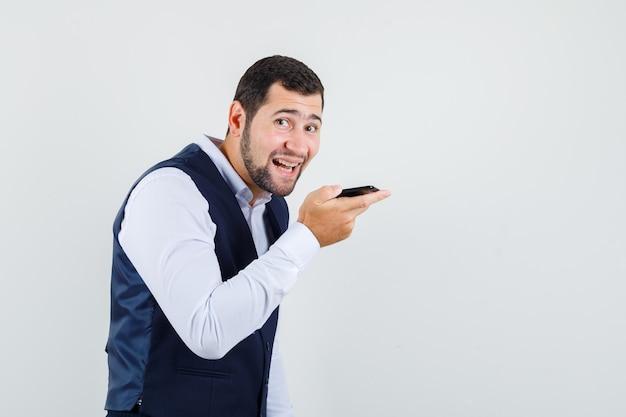 Jeune homme enregistrant un message vocal sur téléphone mobile en costume, gilet