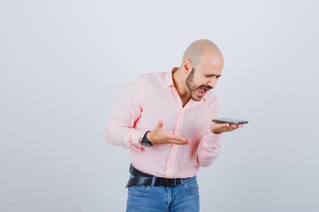 Jeune homme enregistrant un message vocal sur un téléphone portable