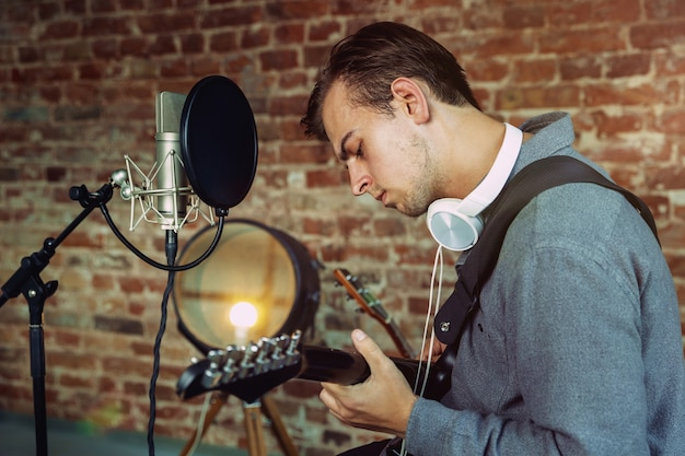 Jeune homme enregistrant de la musique, jouant de la guitare et chantant à la maison