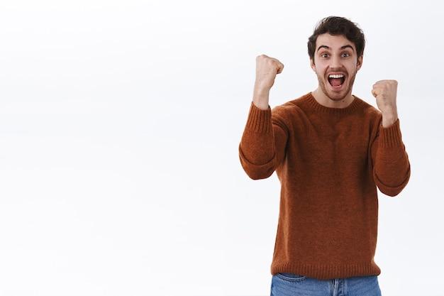 Jeune homme enthousiaste et enthousiaste qui s'enracine pour son équipe préférée, levant les mains