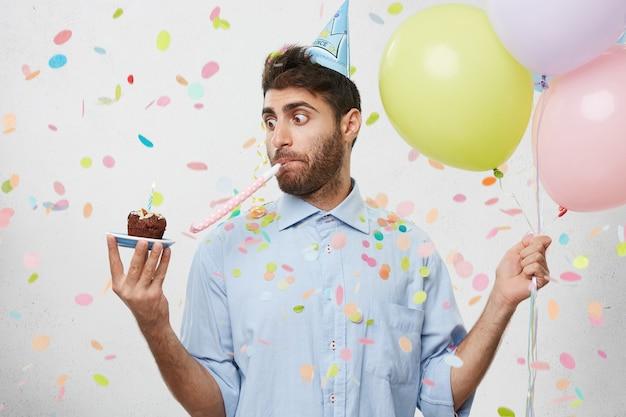 Jeune homme entouré de confettis tenant un petit gâteau et des ballons