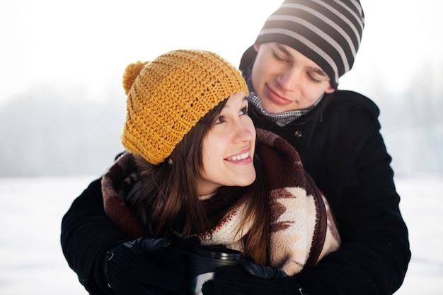 Jeune homme enveloppant sa petite amie dans une couverture