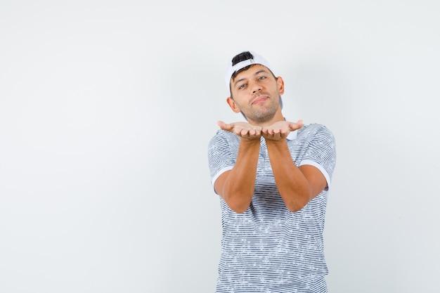 Jeune homme envoyant un baiser soufflant en t-shirt et casquette et à la joie