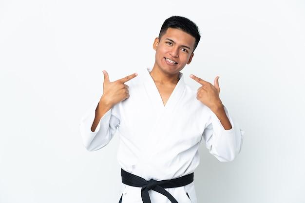 Jeune homme équatorien faisant du karaté isolé sur blanc donnant un geste de pouce en l'air