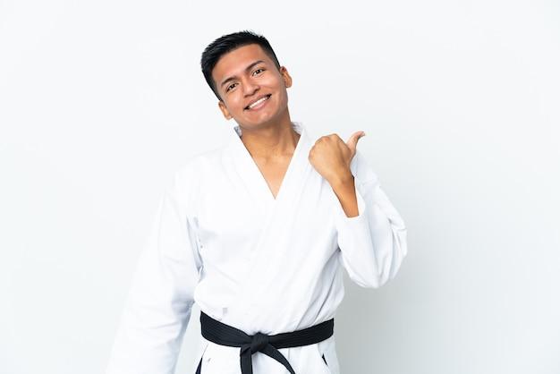 Jeune homme équatorien faisant du karaté isolé sur fond blanc pointant vers le côté pour présenter un produit