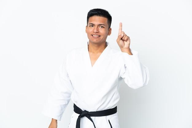 Jeune homme équatorien faisant du karaté isolé sur fond blanc pointant vers une excellente idée