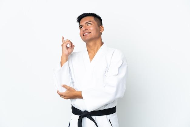 Jeune homme équatorien faisant du karaté isolé sur un mur blanc pointant vers le haut une excellente idée