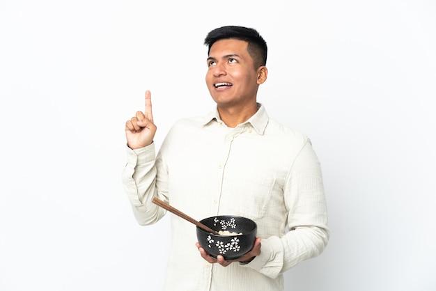 Jeune homme équatorien isolé sur fond blanc dans l'intention de réaliser la solution tout en soulevant un doigt tout en tenant un bol de nouilles avec des baguettes