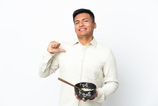 Jeune homme équatorien isolé sur fond blanc fier et satisfait de lui-même tout en tenant un bol de nouilles avec des baguettes