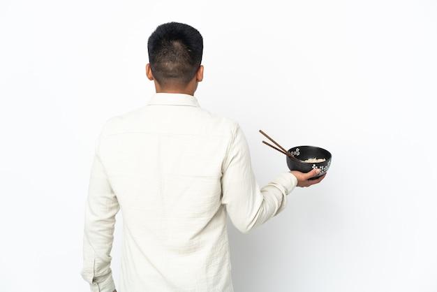 Jeune homme équatorien isolé sur fond blanc en position arrière tout en tenant un bol de nouilles avec des baguettes