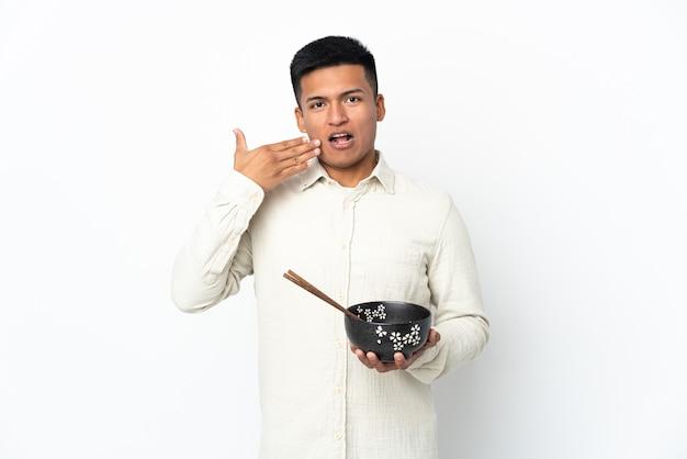 Jeune homme équatorien isolé sur fond blanc tenant un bol de nouilles avec des baguettes et surpris