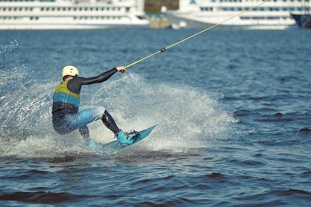 Jeune homme équitation wakeboard sur un lac d'été.