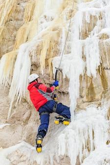 Jeune homme escaladant la glace