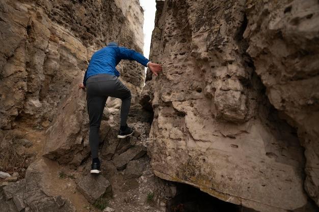 Jeune homme escalade des rochers
