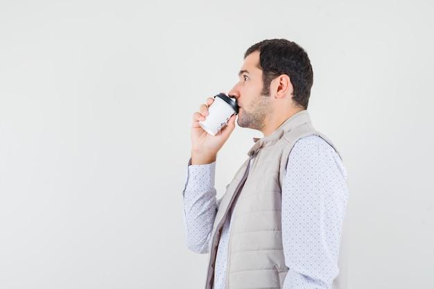 Jeune homme essayant de boire une tasse de café à emporter en veste beige et à la grave, vue de face.