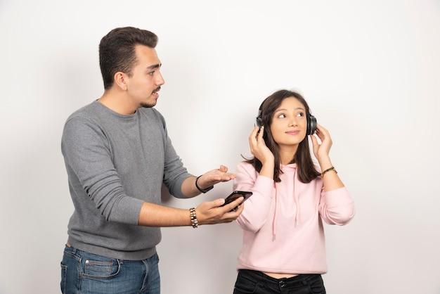 Jeune homme essayant d'obtenir une femme pour regarder son téléphone.