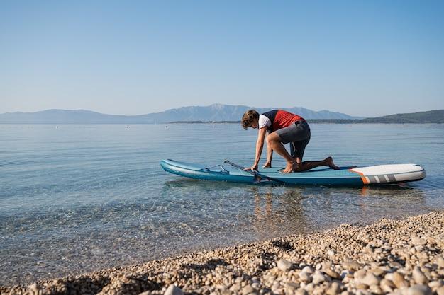 Jeune homme essayant de se lever sur une planche de sup sur la belle mer du matin calme par plage de galets.