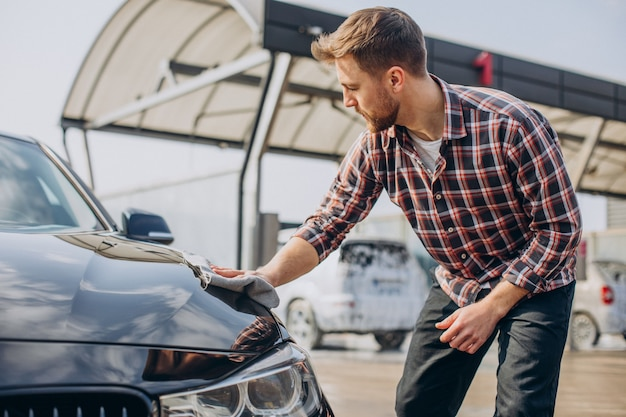 Jeune homme essuyant sa voiture après lavage de voiture