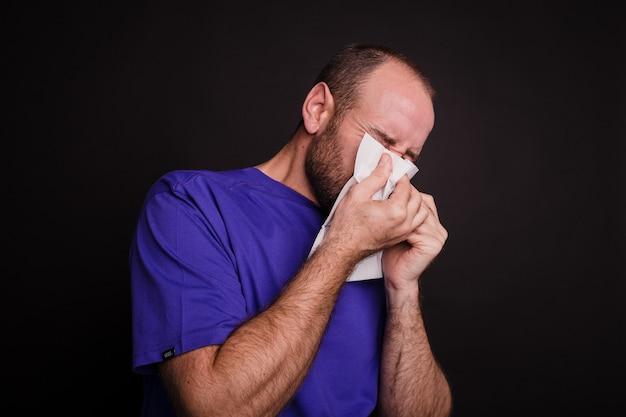 Jeune homme essuyant son nez avec une serviette en papier contre dark