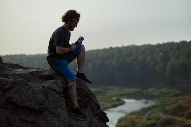 Un jeune homme est assis au sommet d'une montagne et joue du ukulel surplombant la forêt d'automne et la riv...
