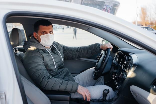 Un jeune homme est assis au volant avec un masque pour sa sécurité personnelle pendant la conduite pendant une pandémie et un coronavirus. épidémie