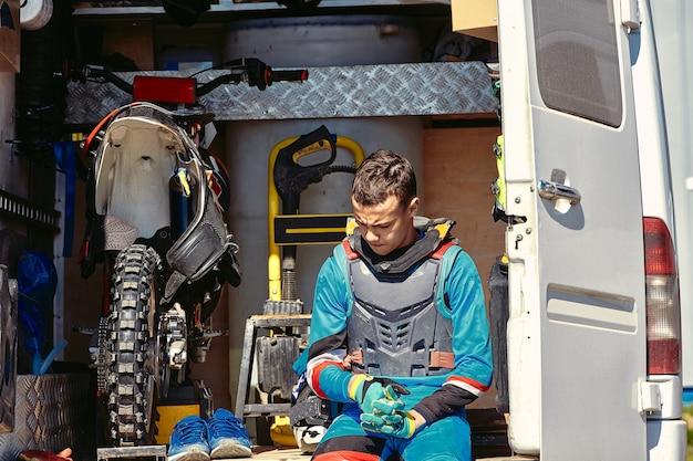 Un jeune homme est assis dans une camionnette avec une moto tout-terrain, une moto, se repose entre les courses.