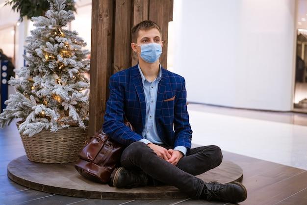 Un jeune homme est assis dans un centre commercial dans un masque médical avec un téléphone à la main près de l'arbre de noël