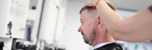 Jeune homme est assis dans une chaise de coiffure et fait une coupe de cheveux en portrait de salon de beauté. concept de services de coiffure pour le développement des petites entreprises.