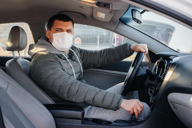 Un jeune homme est assis derrière le volant portant un masque pour sa sécurité personnelle tout en conduisant pendant une pandémie et un coronavirus. épidémie.