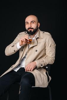 Un jeune homme est assis sur un fond noir et boit une boisson alcoolisée.