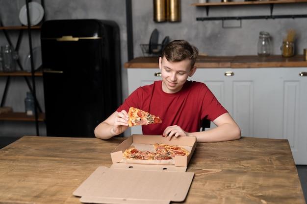 Un jeune homme est assis à une table en bois avec une pizza dans une boîte en carton et tient un morceau de pizza à la main