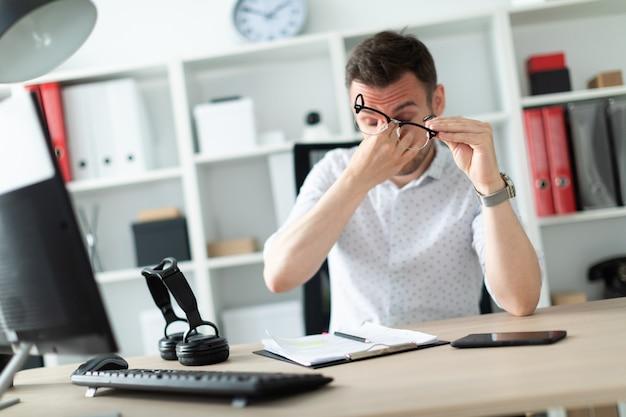 Un jeune homme est assis à une table dans le bureau, enlève ses lunettes et se frotte les yeux.