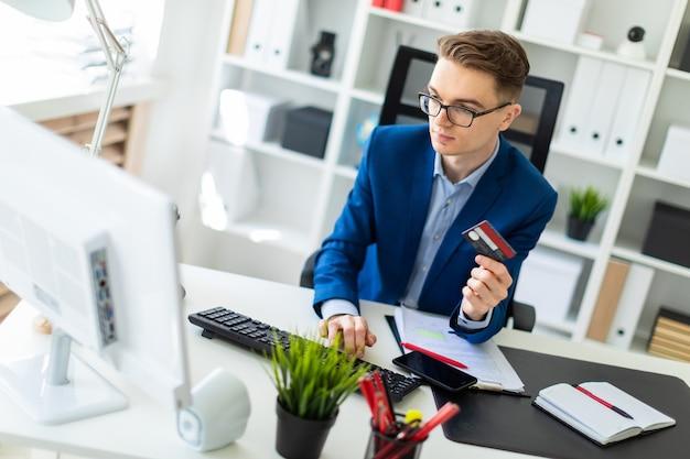 Un jeune homme est assis à une table du bureau, tenant une carte bancaire à la main et tapant un ordinateur.
