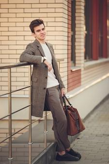 Un jeune homme est debout avec un sac de voyage, gros plan, contre un mur de briques.