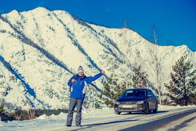Un jeune homme est sur la route et arrête la voiture, derrière la vue sur les montagnes enneigées