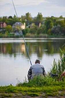 Jeune homme est en train de pêcher sur le lac.