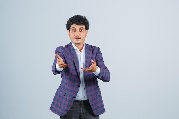 Jeune homme étirant les mains dans un geste perplexe en chemise, veste, pantalon vue de face.