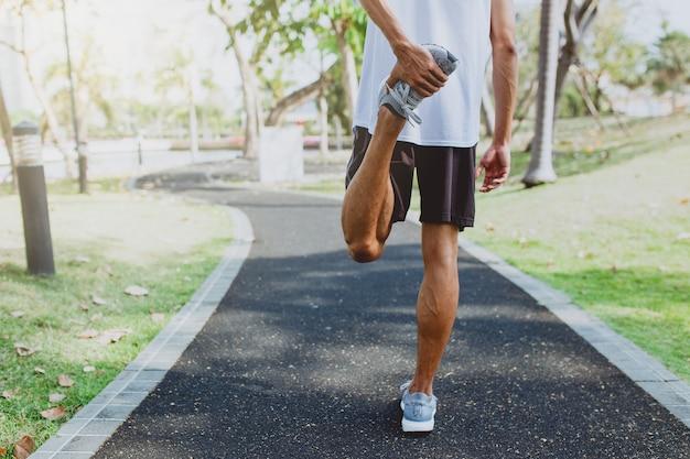 Jeune homme étirement des corps, se réchauffer pour faire du jogging dans un parc public.