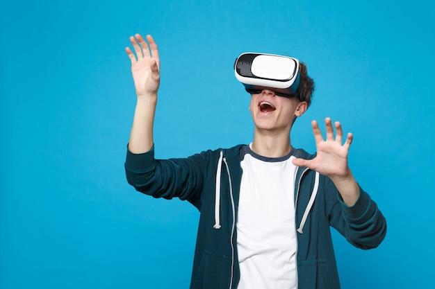 Un jeune homme étonné dans un casque touche quelque chose comme un clic sur le bouton, pointant sur un écran virtuel flottant isolé sur un mur bleu. les gens émotions sincères, concept de style de vie.