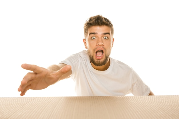 Jeune homme étonné ouvrant le plus gros colis postal isolé sur blanc. modèle masculin choqué sur le dessus de la boîte en carton regardant à l'intérieur.