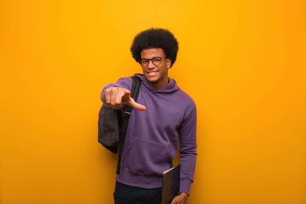 Jeune homme étudiant afro-américain gai et souriant pointant vers l'avant