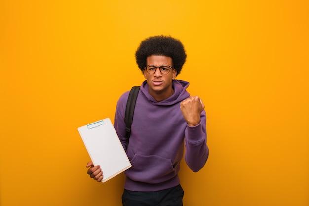 Jeune homme étudiant afro-américain tenant un presse-papiers montrant le poing vers l'avant, l'expression en colère