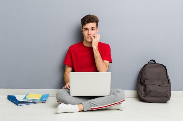 Jeune homme étudiant assis sur le sol de sa maison tenant un ordinateur portable